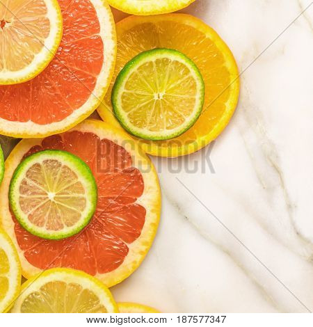 A square photo of vibrant juicy citrus fruits on a white marble texture with copy space. Grapefruit, lime, lemon, and orange slices