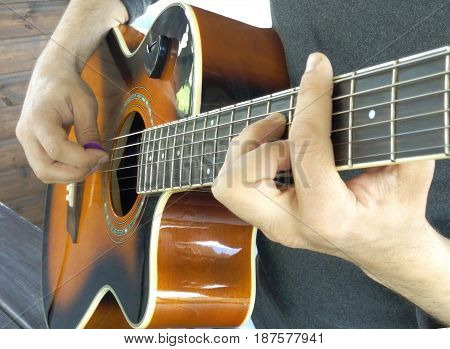 Acoustic guitar. A man plays an acoustic guitar with two hands close-up picture a technique game by a mediator and finger-style