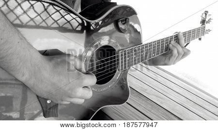 Acoustic guitar plays. A man plays an acoustic guitar with two hands close-up picture black and white photography a technique game by a mediator and finger-style