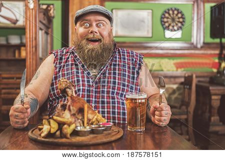 Just unbelievable. Portrait of funny bearded man sitting in pub with a big portion of food and glass of light beer. He holding knife and fork while expressing surprise