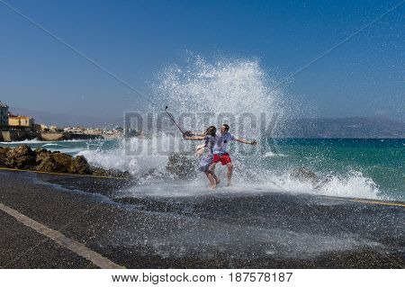 HERAKLION GREECE - JULY 16 2016: A young couple making selfie on the pier during a storm at sea.