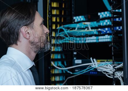 Internet wires. Handsome thoughtful professional engineer standing near the network server and looking at the wires while checking the Internet connection