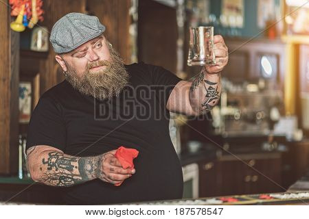 Perfectionism. Tattooed bartender looking at perfect washed glass squinting one eye. He standing at bar counter