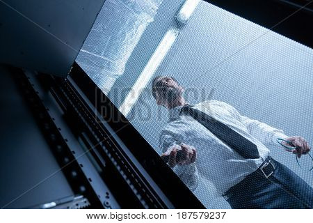 My job. Serious handsome nice man holding the wires and checking the network server while standing behind the metal grid