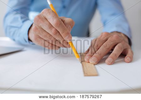 Be accurate. Close up of pencil and ruler in hands of professional engineer holding them while drawing a blueprint