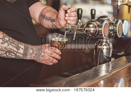 Only tasty beer. Close-up of hands of man filling glass of cold lager from special equipment in pub. Barman standing at counter in bar