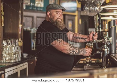 Good mood. Bearded fat bartender pouring beer from tap in big glass in boozer. He looking at camera with slight smile