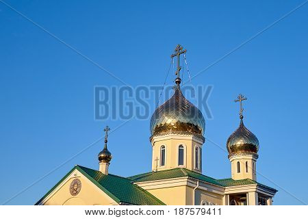 Eastern orthodox crosses on gold domes cupolas againts blue sky without clouds and green roofs