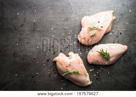 Raw chicken fillet with sea salt pepper and rosemary on . Food background cooking ingredients. Fresh meat. Chicken breast.