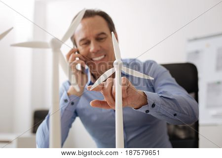 Like what you do. Cheerful professional engineer talking on cellphone with models of wind turbines in the forefront