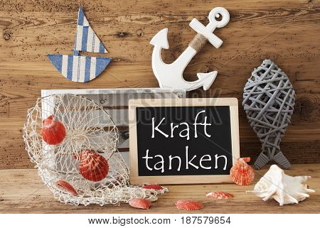 Blackboard With Nautical Summer Decoration And Wooden Background. German Text Kraft Tanken Means Relax. Fish, Anchor, Shells And Fishnet For Maritime Contex.