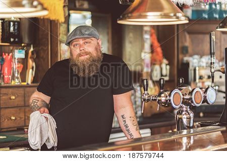 Lazy at work. Portrait of bearded man standing in pub while leaning at counter. He looking at camera playfully