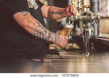 Tasty ale. Close-up of hands with glass of tattooed man pouring light beer from tap. He working as bartender in pub