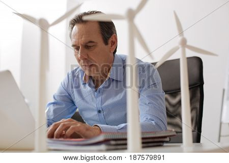 Important work. Pleasant professional engineer using laptop and designing wind turbines while workign in the office