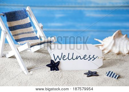 Summer Label With English Text Wellness. Blue Wooden Background. Card With Holiday Greetings. Beach Vacation Symbolized By Sand, Deck Chair And Shell.