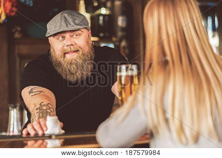 Elegant visitor. Selective focus on cheerful bearded man leaning on counter and laughing while talking with woman. Smiling barman and blonde lady from behind standing in pub