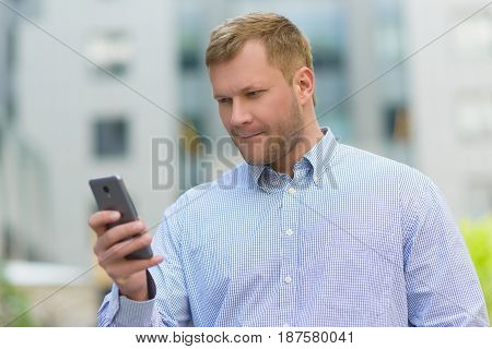 tense businessman looking on his cell phone outdoors.