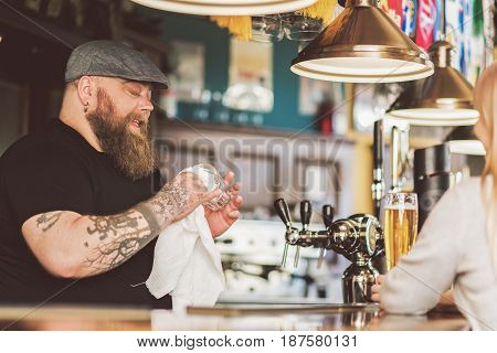 Candid conversation. Obese bartender with beard wiping glass while talking with client. Blonde woman sitting with beer and smiling. Focus on male