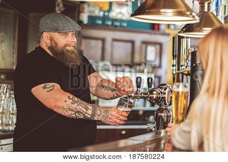 Flirting at work. Selective focus on playful barman pouring glass of beer while talking with charming woman sitting at counter. He looking at girl with delight