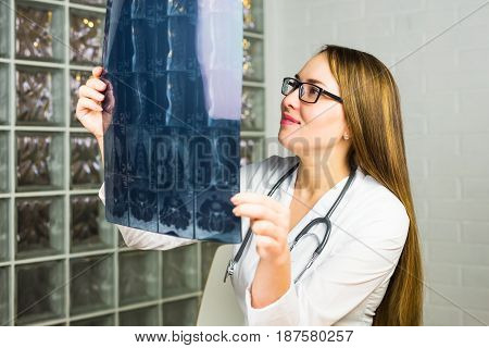 Portrait of intellectual woman healthcare personnel with white labcoat, looking at full body x-ray radiographic image, hospital clinic background. Radiology department.
