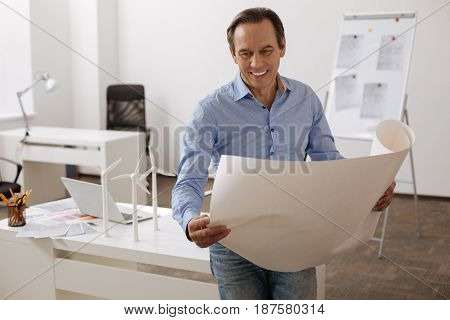 Implement in reality. Positive professional senior engineer holding blueprint and working on the project while standing in the office