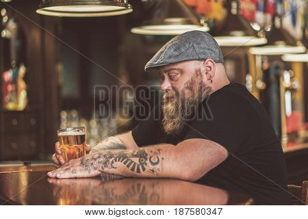 Loneliness. Depressed obese male sitting with mug of beer while leaning at bar counter thoughtfully. He looking at glass sorrowfully