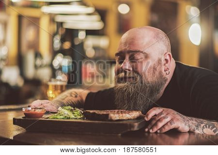 Divine aroma. face of pleasant bearded man sitting at bar counter and sniffing aromatic steak. He enjoying smell with closed eyes