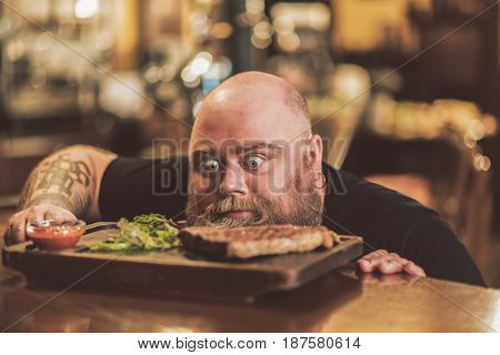Hunger. face of obese male expressing astonishment while looking at succulent steak. He leaning on counter in anticipation