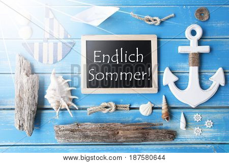 Flat Lay Of Chalkboard On Blue Wooden Background. Sunny Nautic Or Maritime Summer Decoration As Holiday Greeting Card. German Text Endlich Sommer Means Happy Summer