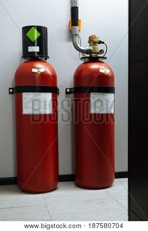 Safety measure. Close up of two big fire extinguishers standing on the floor