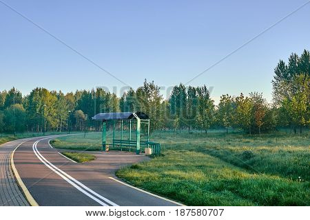 morning village road with road strips, bus stop trees , bushes and sunrise