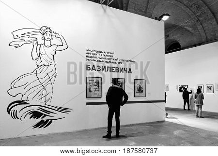 KIEV - UKRAINE - MAY 2017:  Art and book exhibition in Arsenal museum in Kiev. A man views the exposition of the exhibition. Black and white photography