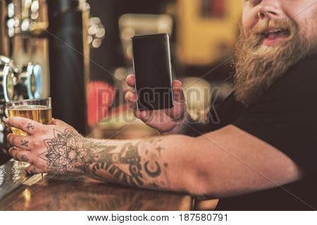 My gadget. Cheerful tattooed guy sitting in pub while holding glass of beer in one hand and mobile phone in other hand. Focus on screen of smartphone
