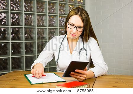 healthcare, technology and medicine concept - smiling female doctor with stethoscope and tablet pc computer