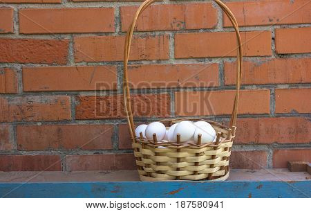 Basket with white eggs on a brick wall background