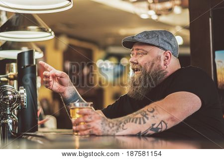 Hey you. Cheerful drunk bearded man holding glass of beer and pointing finger with smiling. He sitting at bar counter gesturing positively