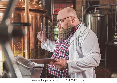 Serious concentrated worker examining brewery machine in pub. He looking at screen while holding notepad and pen