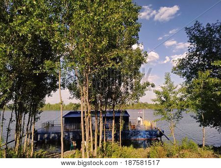 Several loving couples stand near the Dnieper River in Kiev. There is a pleasure ship on the shore. One of the pairs rests on the railing of the ship