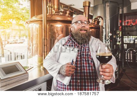 Amazing taste. Joyful satisfied man posing in brewery while making beer. He standing in machinery while holding glass of dark ale