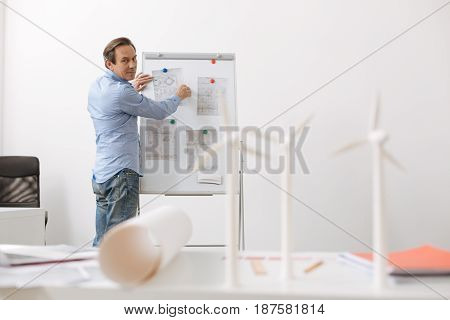 How to implement in life. Professional senior engineer standing near board and studying schemes of wind turbine