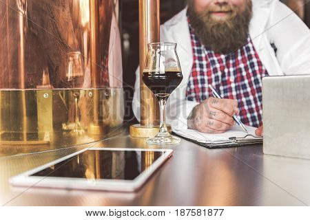 Write down result. Attentive chief brewer making notes in notepad while leaning at table. Focus on glass of dark beer standing in front of man. Tablet computer is near mug