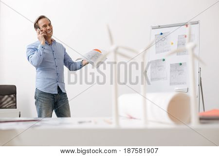 I need you help. Cheerful senior engineer talking on cell phone and discussing project of wind turbines while working in the office