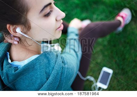 Portrait of young and sporty woman in sportswear sitting with the smartphone and headphones on the grass outside at the park on green field on cloudy day, Dnipro, Ukraine. She is sits on the green meadow between trees and listen music