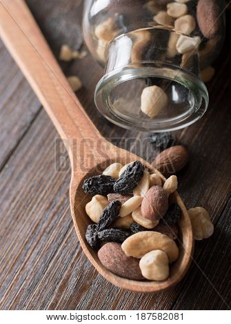 Wooden spoon with nuts, raisins, dried fruits and almonds on a wooden bacground.