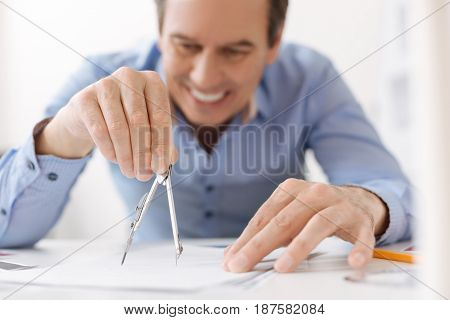 Draw with pleasure. Close up of compasses in hands of professional engineer making a blueprint while working on the project in the office