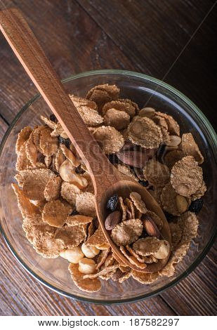 Oat flakes in bowl and wooden spoon with mix nuts and dry fruits on wooden background