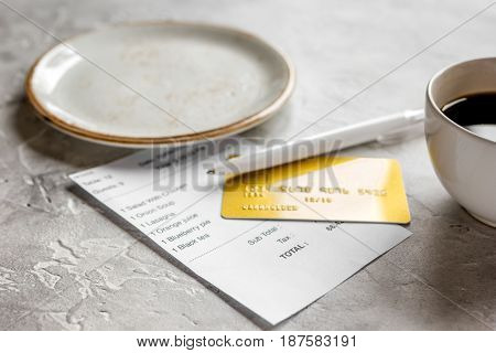 paying check for business lunch in cafe with credit card on stone table background