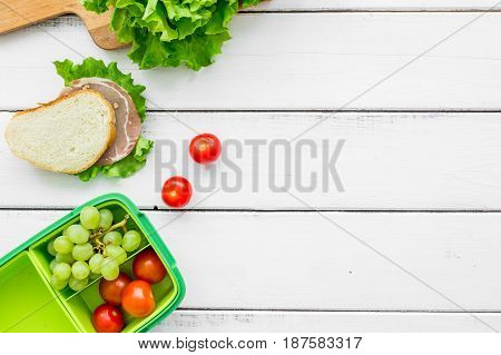 healthy break with lettuce, grape and sandwich in green lunchbox on home wooden table background flat lay mock-up