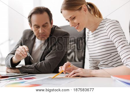 Delighted with the result. Cheerful professional female engineer sitting at the table with her colleague while making drawing and working together