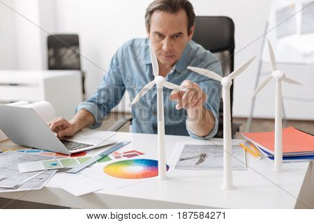 New project. Pleasant professional engineer sitting at the table and using lapotp while working on the project of building wind turbines